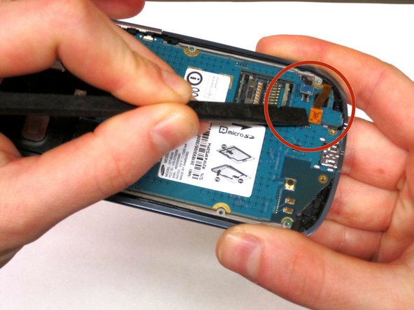 Next, use the spudger and tweezers to remove the speaker at the top of the phone.