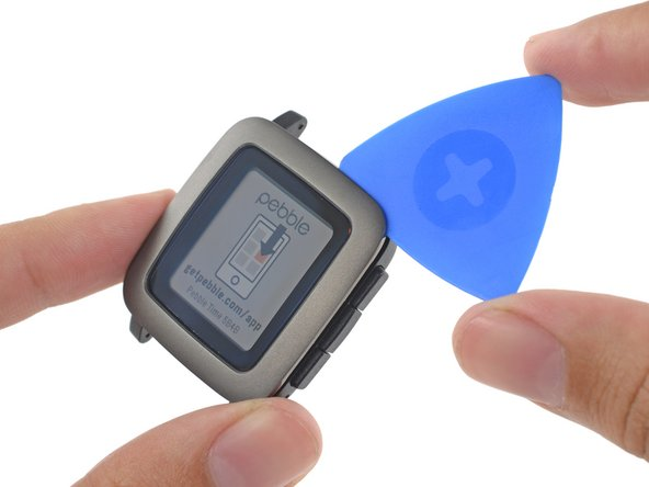 With a minimum amount of heat applied to the front bezel, we use an opening pick to pry along the perimeter of the Pebble Time.