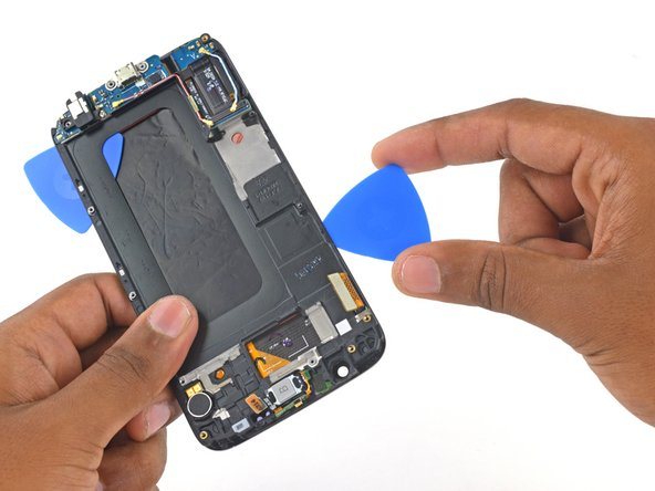 Image 2/3: Insert a second opening pick between the frame and display assembly on the display cable side of the phone.