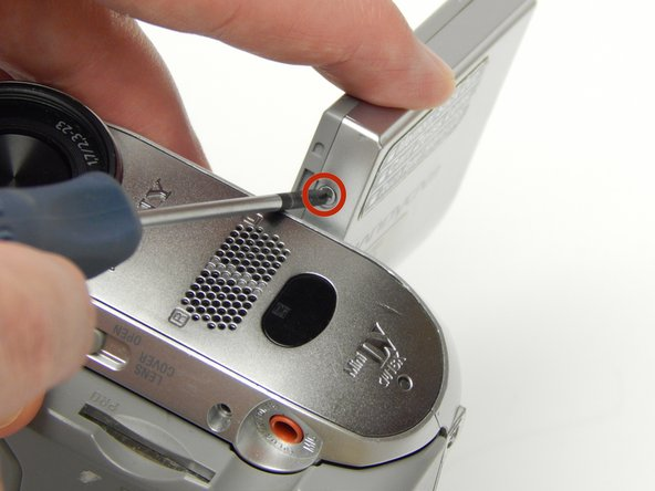 Image 1/3: Turn the LCD screen so you can see the 5 MM Phillips #1 screw on the inside; remove the screw.