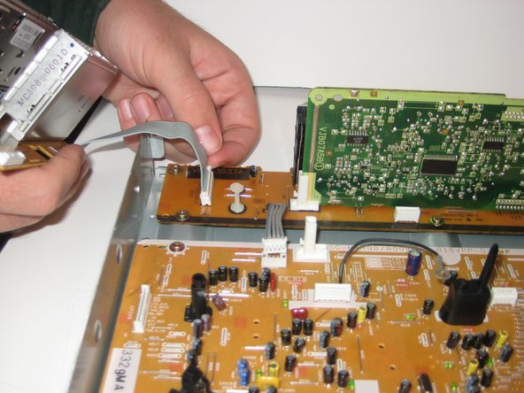 Second, disconnect the electrical strip as seen in image three by pulling the tabs on the plastic piece of the electric strip.