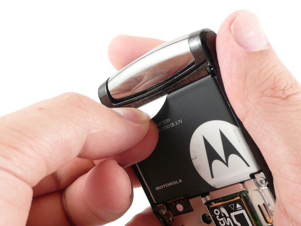 Gently pull the white plastic tab to lift the battery away from the RAZR2.