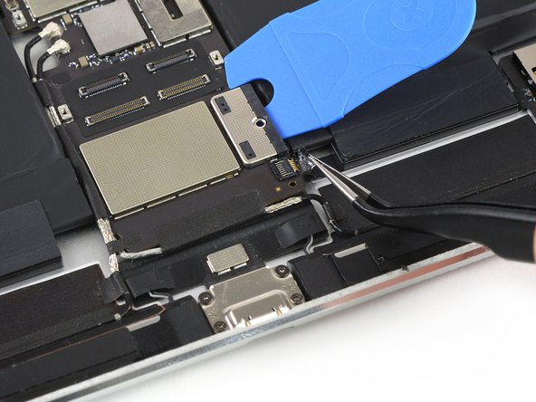 Use a pair of tweezers to peel off the tape that covers the ZIF connector for the SIM card tray flex cable.