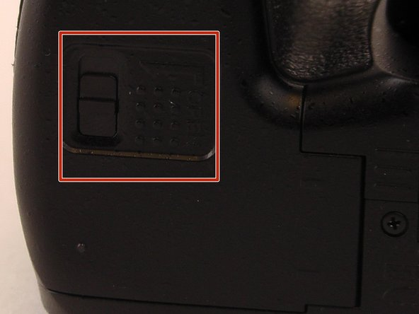 Image 1/2: Push and hold the switch towards the lines.  Then pull away from the camera to open up the battery storage area.