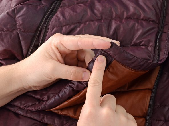 Identify the start of the seam that is holding the zipper in place.