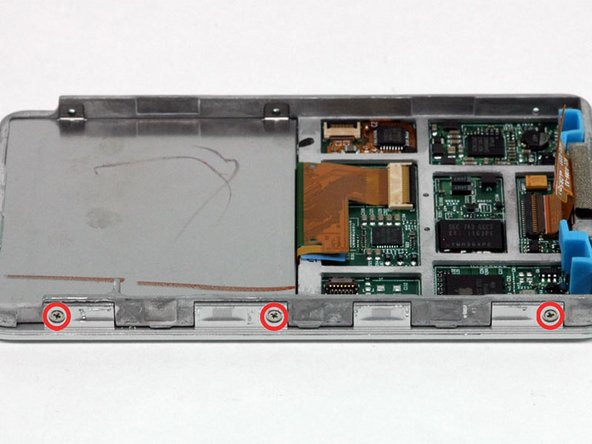 Image 1/1: Rotate the iPod 180 degrees and remove the three Phillips screws securing the front panel to the metal framework on the other side.