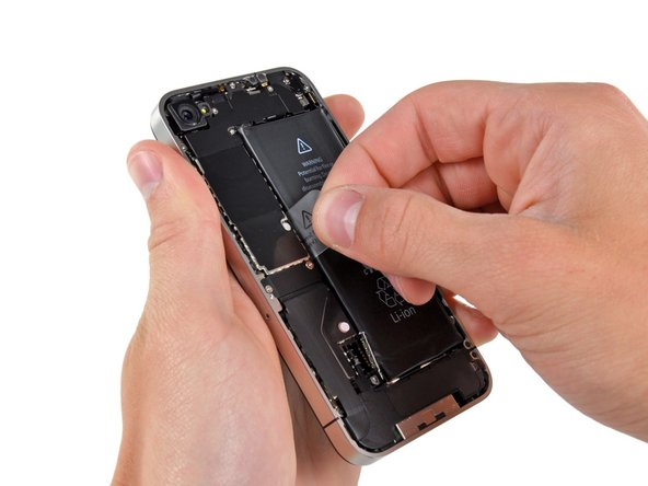 Image 1/3: Use the clear plastic pull tab to gently lift the battery out of the iPhone.