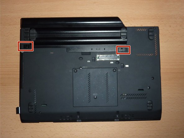 "Locate the two switches that lock the battery. Push the left-hand switch outward into the ""unlocked"" position."