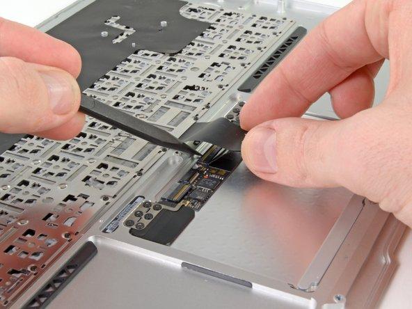 Hebe das Flachbandkabel zur Tastatur mit einer Hand an und klappe gleichzeitig den Sicherungsbügel am ZIF Anschluss des Tastaturkabels mit der Spudgerspitze oder deinem Fingernagel hoch.