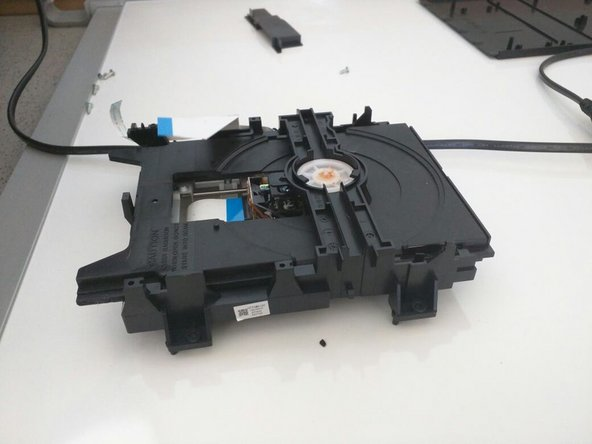 Image 1/2: Disc drive is held on by two screws on the side closer to the black housing. Unscrew these to remove properly.