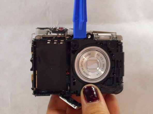 After the battery is out, remove the gray button bar from the top of the camera with the smallest opening tool.