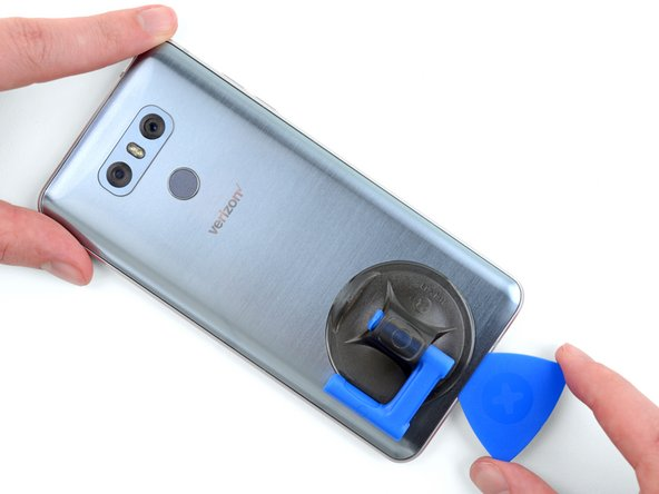 Re-insert the opening pick into the bottom edge of the phone and slide it up the right edge of the phone, cutting through the adhesive holding it in place.