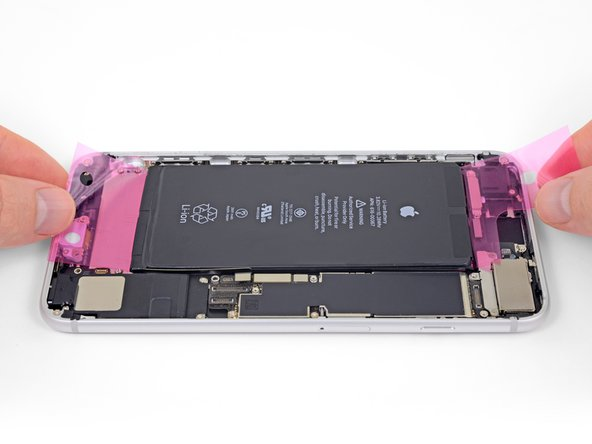 With the large pink release liner still in place, set the battery into your iPhone.