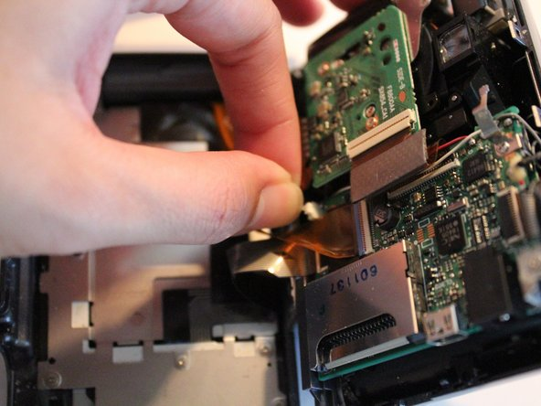 Image 1/3: Pull gently on the white connecting cable to detach it from the main body of the camera.
