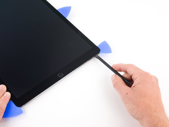 Image 2/3: Slide the halberd spudger along the lower edge of the iPad stopping  short about 1 centimeter before reaching the home button.