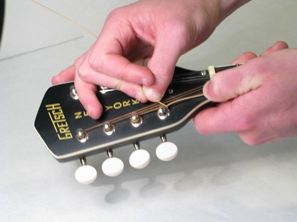 Pull the string tight so that it wraps around the tuning peg.