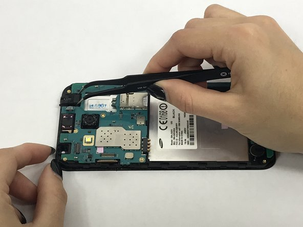 Remove connector tab with spudger then carefully remove headphone jack with tweezers.