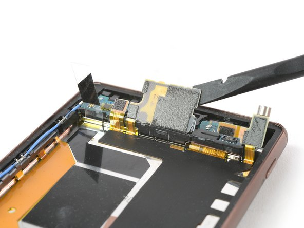 Lift up the main flex cable covering the loudspeaker assembly with a Spudger
