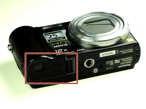Locate the small, hinged door on the bottom of the camera.