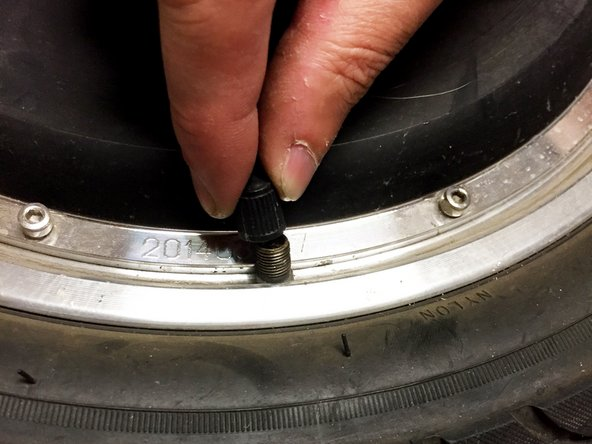 Remove cap from air nozzle on tire.