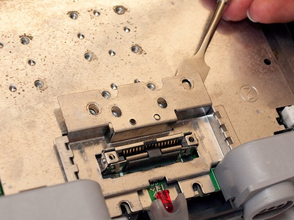 Remove the small metal bracket behind the expansion slot using the spudger.