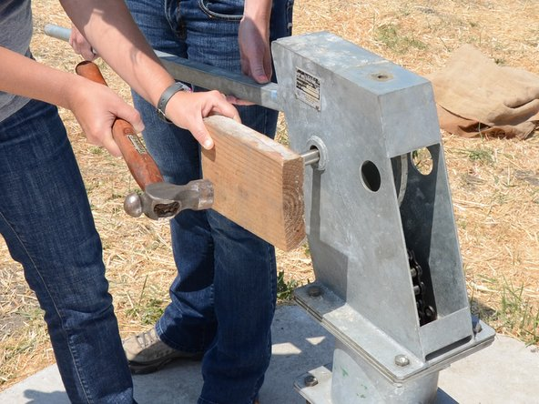 Use a block of wood and hammer to gently tap the axle back into place.