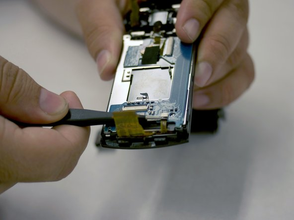 Using metal tweezers, remove the two ribbons connecting the LCD board to the screen.