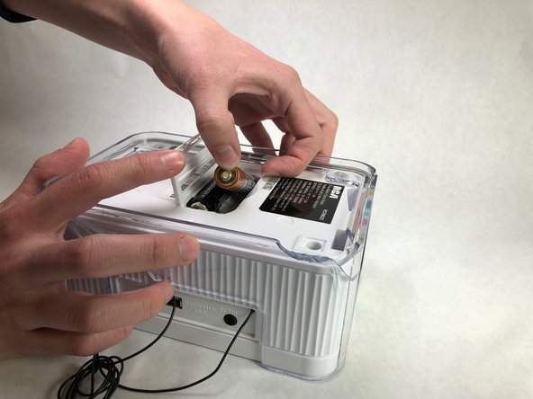 Flip the radio over and use your fingers to lift the battery cover free.