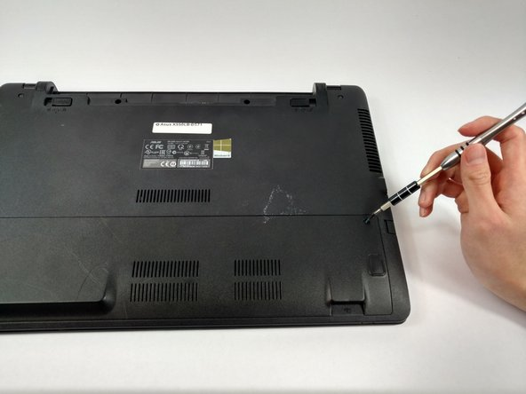 Place the laptop on a flat surface with the bottom side facing upwards.