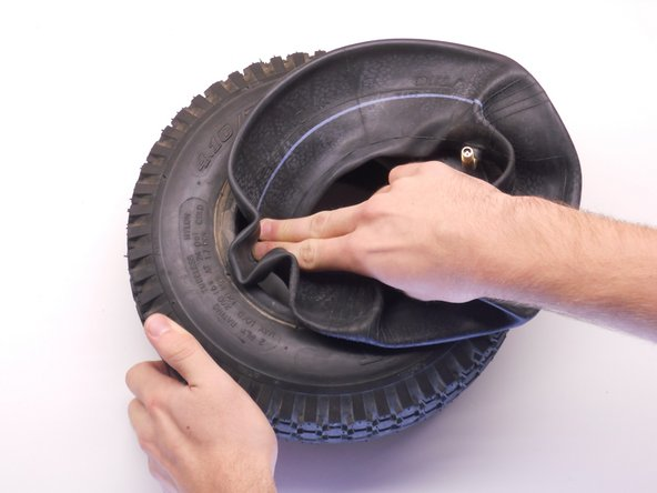Use two fingers to uniformly push the replacement inner tube into the inside of the tire.