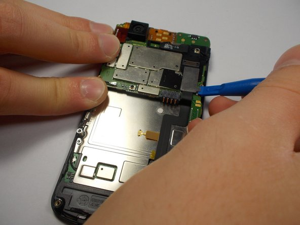 Use your plastic opening tool to disconnect the motherboard/keyboard ribbon cable.