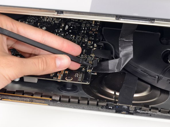 Image 1/3: Carefully pull the display data cable from its socket on the logic board.