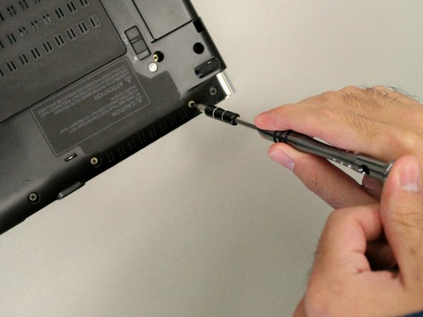 Begin by removing 14 70mm screws from the back cover of the laptop using a Phillips #00 Screwdriver. Do not attempt to remove the back cover just yet though.
