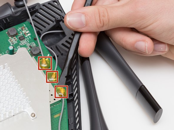 Continue to pry off the last three antenna connections on the upper right portion of the motherboard.