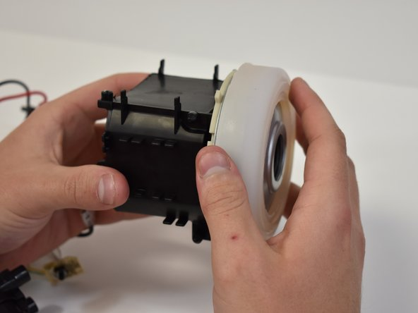 Grasp the vacuum motor and housing and pull them apart.
