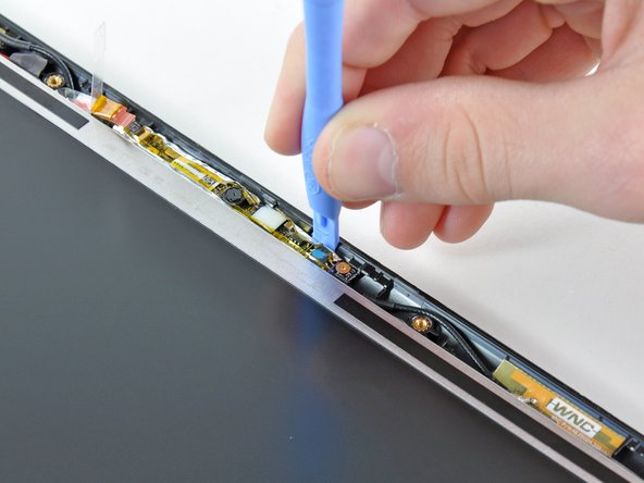 Use the edge of a plastic opening tool to pry the right side of the camera board away from the display assembly.
