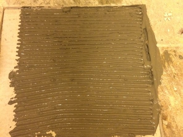 After the mortar is placed on the flooring, use the notched side of the trowel to apply the mortar to the flooring in it's final form. (Even rows visible in mortar.)