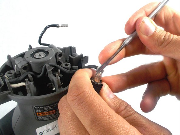 Using a spudger such as the one shown, carefully pry open the connectors as shown just enough to slide the prongs of the switch out.