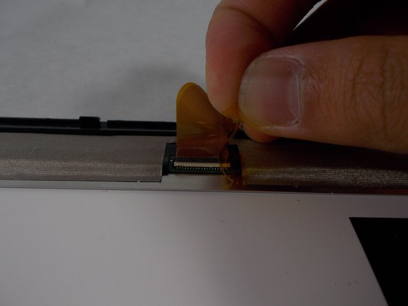 Disconnect the ribbon cable from the screen by lifting up on the connection and pulling out the ribbon cable.