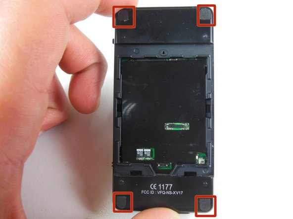 Remove the four corner plastic covers on the back of the device using the plastic opening tool.