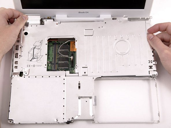 Image 1/1: If your iBook has Bluetooth, as discussed in the previous step, you will need to slide the antenna through the lower I-shaped hole in the shield before completely removing the shield.