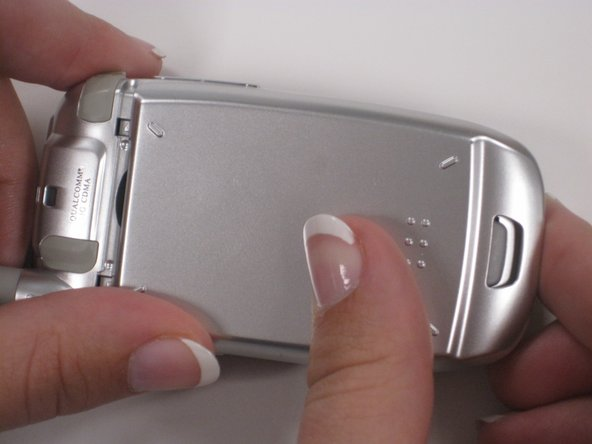 Press down and slide the back panel to remove it from the phone, while continuing to hold the gray button.