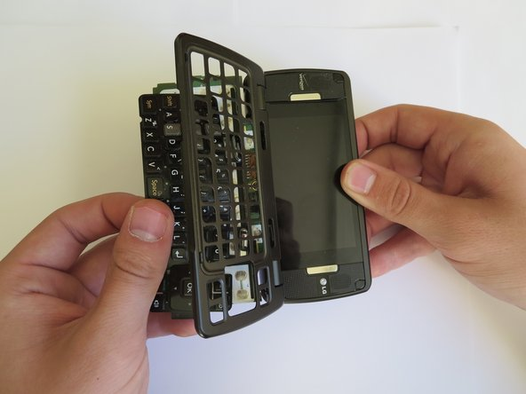 Image 1/1: Using your thumbs, gently separate the motherboard from the frame, and the keyboard will fall out.