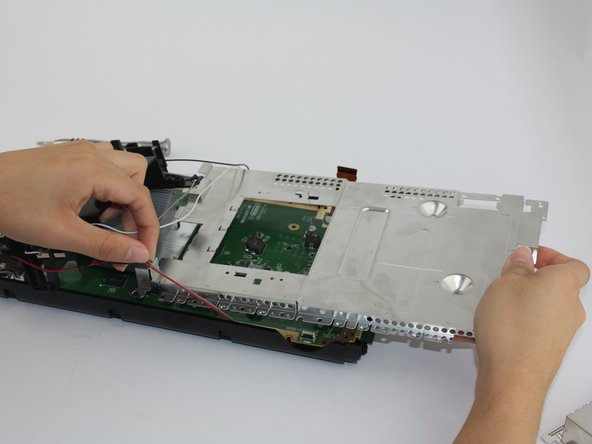 Remove the silver shielding plate once all screws are removed. Be careful when pulling it under the affixed antenna cables.