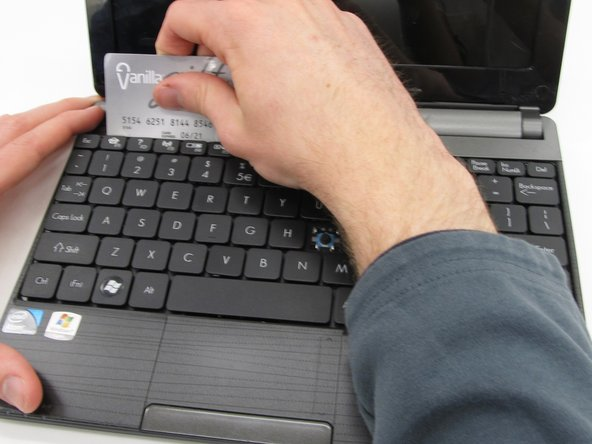 Begin to slide the plastic card under the top edge of the keyboard. You will hear popping sounds and the keyboard will eventually be released.