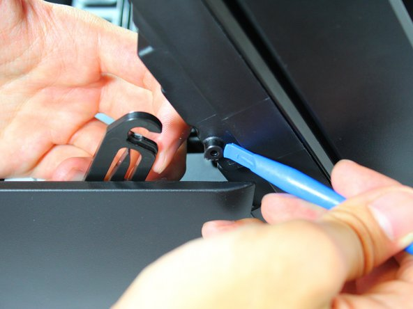 Unhook the clip supporting the cartridge access door by using a plastic opening tool to get under the clip and using another hand to pull the clip from its hook.