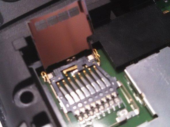 La carte SD elle-même glisse dans et hors de la couverture métallique.