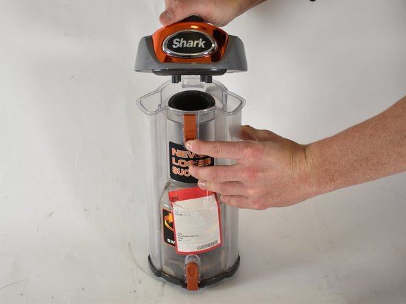 A dust filter is located within the dust cup.   To access it, open the dust cup  by pressing the orange tab on the front and  pulling up on the handle.