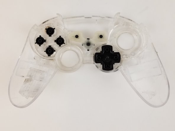 Pick up the controller front plate and carefully turn it over so that the buttons left in it will fall out.