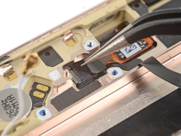 Use tweezers to peel the tape covering the fingerprint sensor cable connector near the bottom edge of the phone.